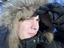 Uomo che guarda qualcosa nella foresta di inverno Fotografia Stock
