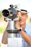 Uomo che guarda tramite il telescopio Fotografia Stock Libera da Diritti