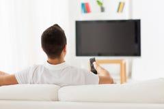 Uomo che guarda TV e che cambia i canali a casa Immagine Stock