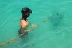 Uomo che guida nell'ambito del ritrovamento dell'acqua e che cerca animale acquatico nel mare fotografia stock libera da diritti