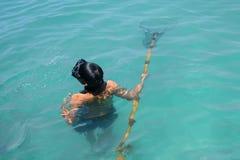 Uomo che guida nell'ambito del ritrovamento dell'acqua e che cerca animale acquatico nel mare immagine stock libera da diritti