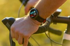 Uomo che guida una bici con il cardiofrequenzimetro dello smartwatch immagini stock libere da diritti