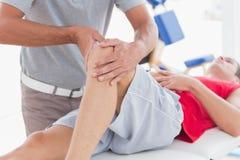 Uomo che ha massaggio del ginocchio Fotografie Stock Libere da Diritti