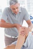 Uomo che ha massaggio del ginocchio Immagine Stock