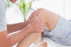 Uomo che ha massaggio del ginocchio Immagine Stock Libera da Diritti