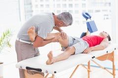 Uomo che ha massaggio della gamba Immagine Stock