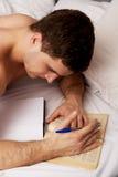 Uomo che impara all'esame nel suo letto immagine stock
