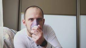 Uomo che inala attraverso la maschera dell'inalatore nella stanza stock footage