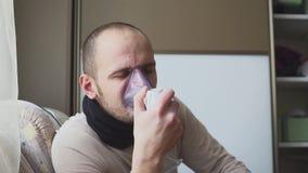 Uomo che inala attraverso la maschera dell'inalatore nella stanza video d archivio