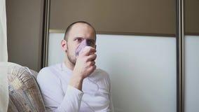 Uomo che inala attraverso la maschera dell'inalatore nella stanza archivi video