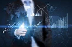 Uomo che indica ai grafici finanziari Fotografia Stock