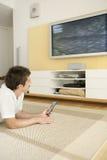 Uomo che indica sul pavimento che guarda TV Fotografia Stock