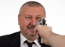 Uomo che indica una pistola sull'uomo d'affari fotografia stock libera da diritti
