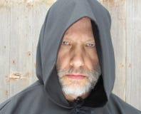 Uomo che indossa fissare incappucciato nero del capo Immagine Stock