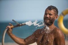Uomo che innaffia con il tubo flessibile Fotografia Stock