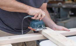 Uomo che insabbia un progetto di DIY fotografia stock