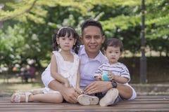 Uomo che insegna ai suoi bambini a risparmiare soldi nel porcellino salvadanaio fotografia stock libera da diritti