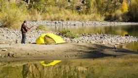 Uomo che installa la sua tenda per accamparsi archivi video