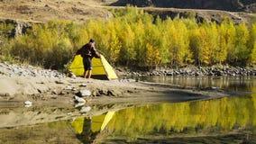 Uomo che installa la sua tenda per accamparsi stock footage