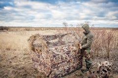 Uomo che installa la tenda di caccia nel campo rurale Fotografia Stock