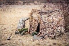 Uomo che installa la tenda di caccia nel campo rurale fotografia stock libera da diritti