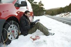 Uomo che installa le catene di neve immagini stock libere da diritti