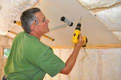 Uomo che installa muro a secco sul soffitto Fotografia Stock Libera da Diritti