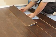 Uomo che installa nuova pavimentazione di legno laminata Fotografia Stock