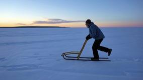 Uomo che kicksledding per restare adatto durante i periodi invernali fotografia stock libera da diritti