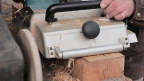 Uomo che lavora ad una piallatrice di legno I chip volano nel lato diverso dalla piallatrice stock footage