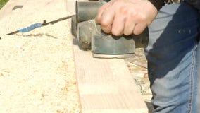 Uomo che lavora ad una piallatrice di legno I chip volano nel lato diverso dalla piallatrice archivi video