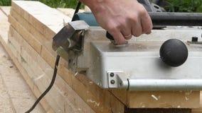 Uomo che lavora ad una piallatrice di legno I chip volano nel lato diverso dalla piallatrice Movimento lento stock footage