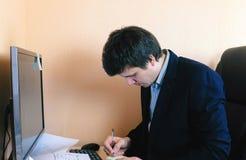 Uomo che lavora al calcolatore Scrive qualcosa alla carta dell'autoadesivo Fotografia Stock Libera da Diritti