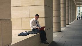 Uomo che lavora al computer portatile all'esterno stock footage