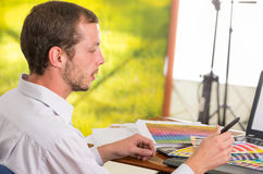 Uomo che lavora al computer portatile mentre sostenendo pantone Fotografia Stock Libera da Diritti