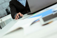 Uomo che lavora al computer portatile nel suo luogo di lavoro immagini stock libere da diritti