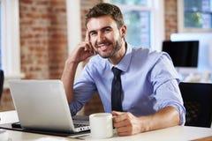 Uomo che lavora al computer portatile in ufficio contemporaneo Fotografie Stock