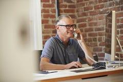 Uomo che lavora al computer in ufficio contemporaneo Fotografie Stock