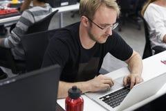 Uomo che lavora al suo computer portatile Fotografia Stock Libera da Diritti