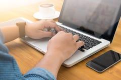 Uomo che lavora al suo computer portatile Immagini Stock