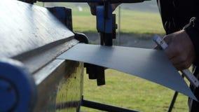 Uomo che lavora alla lamina di metallo del tetto nella costruzione del sito stock footage