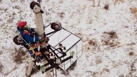 Uomo che lavora alla linea elettrica di energia di riparazione e della stazione sulla torre video d archivio