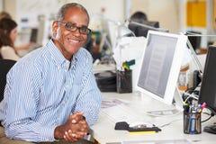 Uomo che lavora allo scrittorio in ufficio creativo occupato Immagine Stock