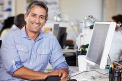 Uomo che lavora allo scrittorio in ufficio creativo occupato Fotografia Stock