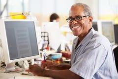 Uomo che lavora allo scrittorio in ufficio creativo occupato immagini stock