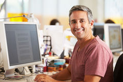 Uomo che lavora allo scrittorio in ufficio creativo occupato Immagini Stock Libere da Diritti