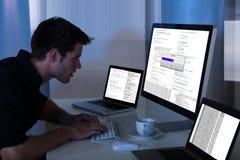 Uomo che lavora con il computer ed il computer portatile Immagine Stock Libera da Diritti