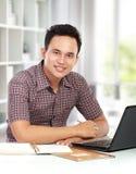 Uomo che lavora con il computer portatile al suo scrittorio Immagine Stock Libera da Diritti