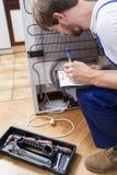 Uomo che lavora con il frigorifero rotto Fotografie Stock