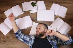 Uomo che lavora con il libro sul pavimento Immagine Stock
